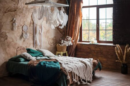 Stylish room interior with large comfortable bed. Beige and white dream catchers and feathers hanging above gypsy or hippie slyle bed in dark autumn bedroom interior