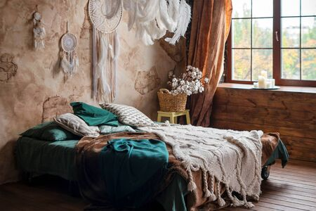 Stylish room interior with large comfortable bed. Beige and white dream catchers and feathers hanging above gypsy or hippie slyle bed in dark autumn bedroom interior 写真素材