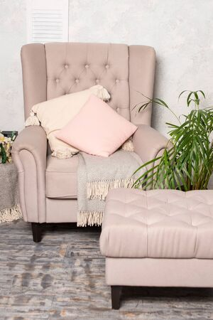 Stylish beige armchair with pink pillows in a bright minimalist interior