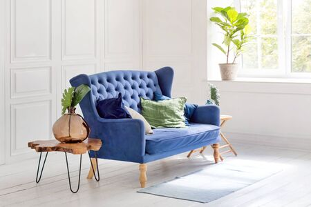 Comfortable classic blue couch with pillows and wooden coffee table in simple white apartment. Reklamní fotografie