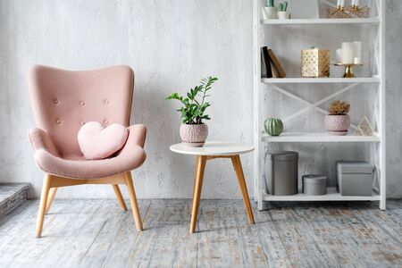 Stylish pink armchair with heart shaped pillow in a bright minimalist interior
