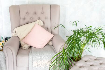 Stylish beige armchair with pink pillows in a bright minimalist interior. Reklamní fotografie