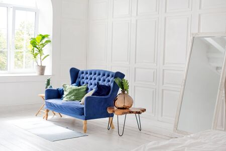 Comfortable classic blue couch with pillows and wooden coffee table in simple white apartment