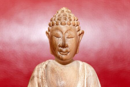 Wooden statue of Buddha, symbol of Buddhism on red background. Free copyspace for text. Reklamní fotografie