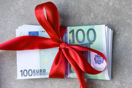 Hundred euro banknotes on a stack with red bow. Gift, bonus or reward concept.