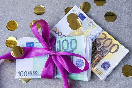 Euro banknotes on a stacks with violet bow. Gift, bonus or reward concept.
