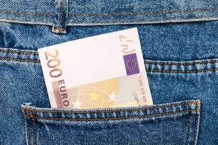 Euro banknotes in jeans back pocket. Forgotten money, nest egg. Concept of saving or spending money. Euro bills falling out. Easy for pickpocket thief to steal the money 写真素材