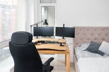 Bedroom interior with a study corner. Large double bed and a desk with a computer and a rolling chair. Home office, freelance work Stockfoto