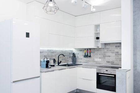 Modernes weißes Kücheninterieur. Zeitgenössisches Interieur mit Loft-Elementen. Standard-Bild