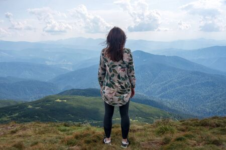 Girl traveling in mountains alone, calm scene. Walking outdoors, woman hiker on mountain top. Back view over landscape. Wanderlust theme. Carpathian mountains, view from the mountain Hoverla, Ukraine