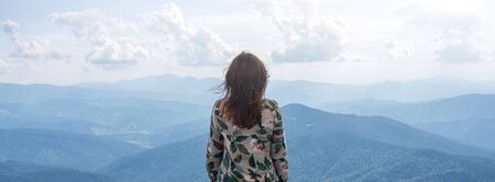 Girl travel in mountains alone, calm scene. Walking outdoors, woman hiker on a top of a mountain. Back view over landscape. Wanderlust theme