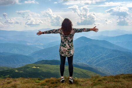 Girl traveling in mountains alone, standing with hands up achieving the top, welcomes a sun. Walking outdoors, woman hiker on mountain top. Wanderlust theme. Carpathian mountains, Hoverla, Ukraine.