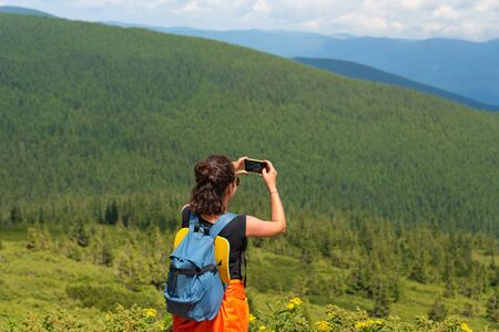 Woman wanderlust photographing scenery nature landscape on smartphone in the mountains. Young female taking photo on cellular. Nature photographer tourist shoots while standing on top of the mountain.