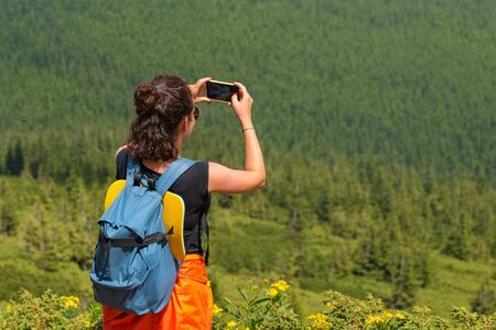Woman wanderlust photographing scenery nature landscape on smartphone in the forest. Young female taking photo on cellular. Nature photographer tourist shoots while standing on top of the mountain.