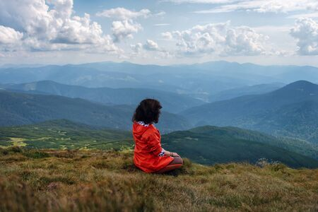 Yoga woman sit in lotus pose on mountain peak. Woman tourist practices yoga and meditates on the mountain. Resting on the highest hill.