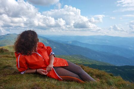 Women sitting at the top of the mountain looking at the valley and mountains. Resting on the highest hill. Wanderlust theme. Carpathian mountains, view from the mountain Hoverla, Ukraine