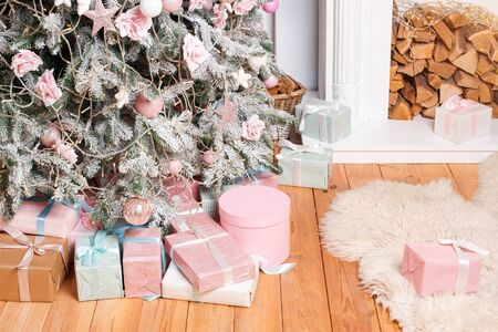 Beautiful Christmas gift boxes on floor near fir tree in room with fireplace. Christmas presents and decoration. Happy Winter Holidays. Stock Photo