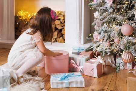 Little girl opening a Christmas gift, Christmas tree and fireplace on background. Christmas presents and decoration.Happy Winter Holidays.