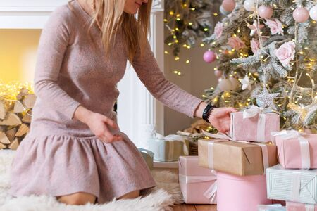 Woman opening a Christmas gift, Christmas tree and fireplace on background. Christmas presents and decoration. Happy Winter Holidays.