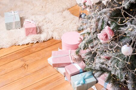 Beautiful Christmas gift boxes on floor near fir tree in the room. Christmas presents and decoration. Happy Winter Holidays. Stock Photo