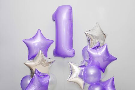 Decoration for 1 years birthday, anniversary. Bunch of gel-shaped violet balloons and stars on light background. Symbol of happy childhood, first birthday party