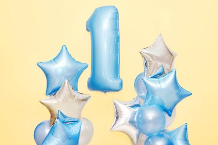 Decoration for 1 years birthday, anniversary. Bunch of gel-shaped blue balloons and stars on yellow background. Symbol of happy childhood, first birthday party Stock Photo
