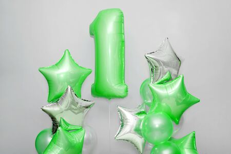 Decoration for 1 years birthday, anniversary. Bunch of gel-shaped green balloons and stars on light background. Symbol of happy childhood, first birthday party