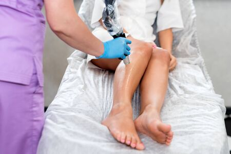 Laser epilation on beautiful female legs at beauty clinic. Hair removal cosmetology procedure. Laser epilation and cosmetology. Cosmetology and SPA concept