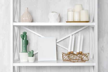 Wooden shelving unit with decor near grey wall. Bookcase with photo frame mockup and candles, living room interior details. Stock Photo - 132186121