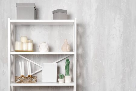 Wooden shelving unit with decor near grey wall. Bookcase with photo frame mockup and candles, living room interior details. Stock Photo - 132185844