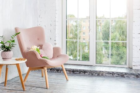 Stylish pink armchair with heart shaped pillow in a bright minimalist interior. Stock Photo