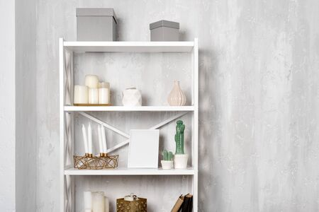 Wooden shelving unit with decor near grey wall. Bookcase with photo frame mockup and candles, living room interior details.