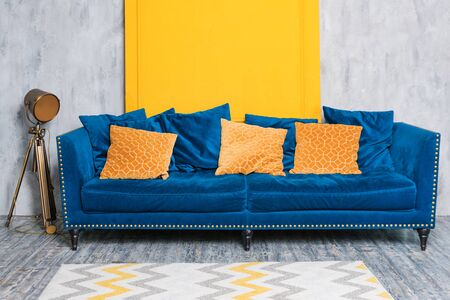 Comfortable classic blue couch with orange pillows in simple minimalist apartment, living room interior details