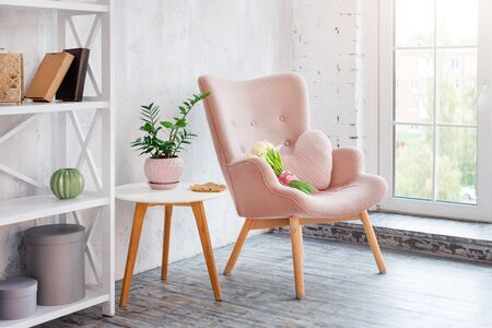 Stylish pink armchair with heart shaped pillow in a bright minimalist interior. Wooden shelving unit with decor near grey wall. Bookcase with candles, living room interior details.