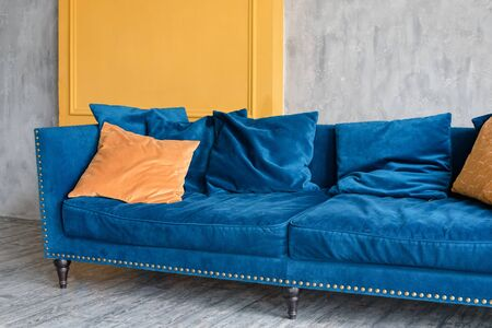 Comfortable classic blue couch with orange pillows in simple minimalist apartment.