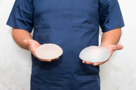 Doctor holding silicone implant for breast augmentation, space for text. Plastic surgeon hands holding silicon breast implants. Cosmetic surgery.