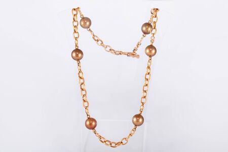 Luxury necklace made of gold with diamonds and pearls on a stand.