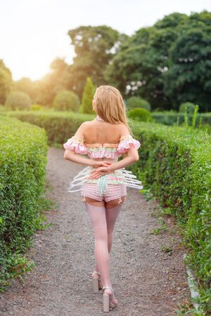 Sexy blonde woman wearing beautiful lingerie with stockings and corset, walking in garden labyrinth, searching the exit. Girl in underware posing outdoors. Female model fitted like a doll, barbie
