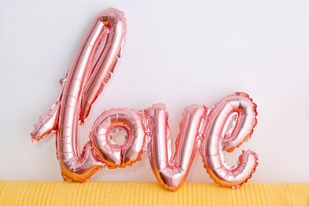 Love word from pink inflatable balloon on white background. The concept of romance, Valentines Day. Love rose gold foil balloon.