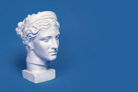 Marble head of young woman, ancient Greek goddess bust isolated on pink background. Gypsum copy of statue Diana head. 免版税图像