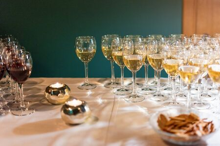 Glasses of wine, standing in a row. Party, celebrating theme. Alcoholic drinks stand on the bar. Wine glasses. 免版税图像