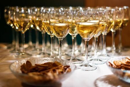 Glasses of white wine, standing in a row. Party, celebrating theme. Alcoholic drinks stand on the bar. Wine glasses.