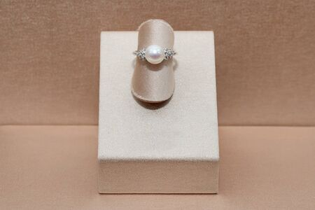 Beautiful diamond gold ring with shine sphere pearl displayed on a stand. Luxury jewelry. 免版税图像