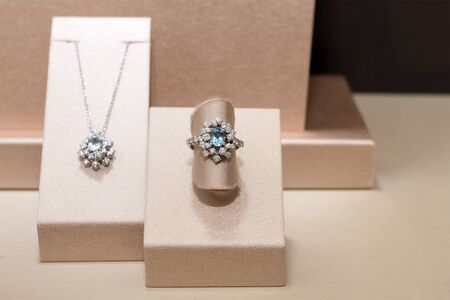 Diamond ring and necklace with blue precious gems. White golden ring on stand. Fashion luxury accessories. 免版税图像