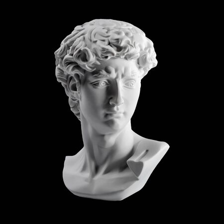 Gypsum statue of David's head. Michelangelo's David statue plaster copy isolated on black background. Ancient greek sculpture, statue of hero.