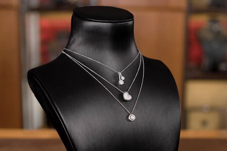 Necklaces made of white gold with diamonds on a stand in fashion jewelry boutique. Black stand neck with luxury jewelry, women accessories in store window