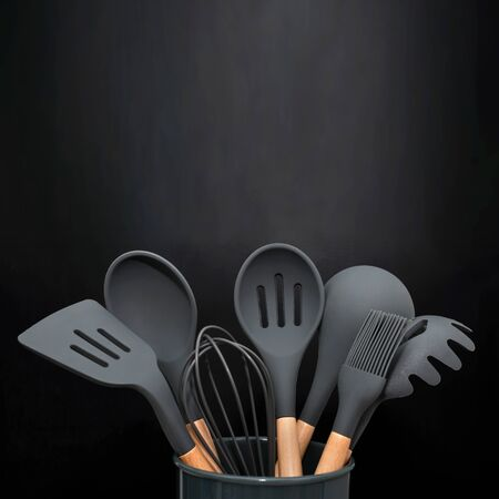 Kitchen utensils background with copyspace, home kitchen decor concept, black kitchen tools, rubber accessories in container.Restaurant, cooking, culinary, kitchen theme. Silicone spatulas and brushes