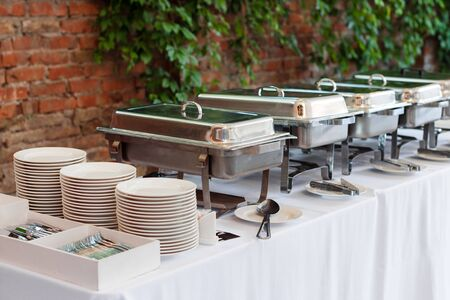 Buffet heated trays standing in line ready for service. Outdoors buffet restaurant, the hotel restaurant.