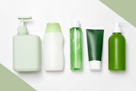 Different size and shapes containers for cleanser toner tonic conditioner, soap and shampoo on white and green background. Natural organic beauty products, blank label package, branding mock-up.