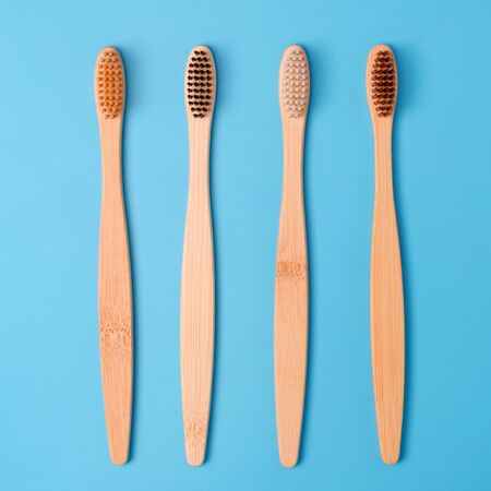 Bamboo toothbrushes on blue background. Eco friendly daily oral hygiene, teeth care and health. Cleaning products for mouth. Dental care concept. Imagens